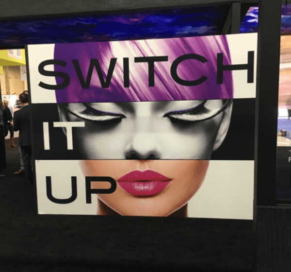 Sample Fabric Graphics Display at Globalshop showing a womans head split into three different colours with the phrase switch it up printed in front