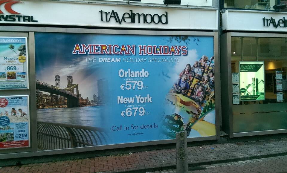 Window graphic at Travelmood shop showing dream deals to America