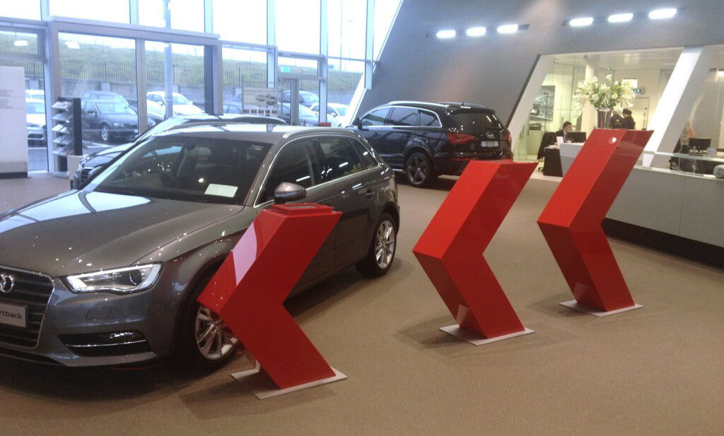 Bespoke red acrylic 3d arrows that are displayed beside showroom cars in an Audi garage