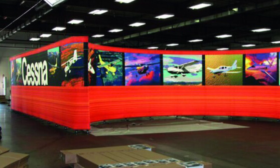 An exhibitions display for Cessna which has a red fabric wall with plane designs printed through it