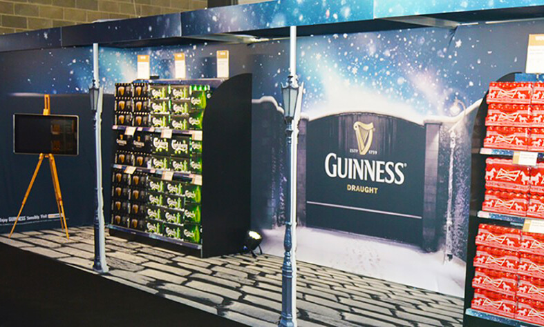 An exhibitions display for guinness that depicts the gates of the guinness brewery with a cobblestone printed carpet