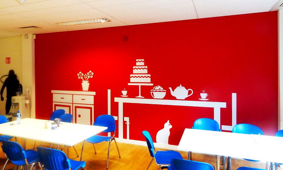 Wall graphic at Virgin Media Canteen printed with a silhouette of a table with tea and cakes and a cat