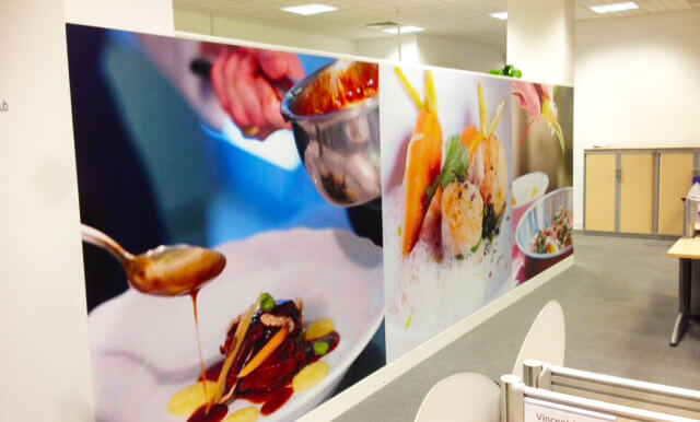 wall graphic in an office depicting a person dripping sauce on a meal and vegetables