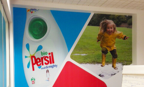 Wall graphic that shows a child playing outside beside a Persil bottle